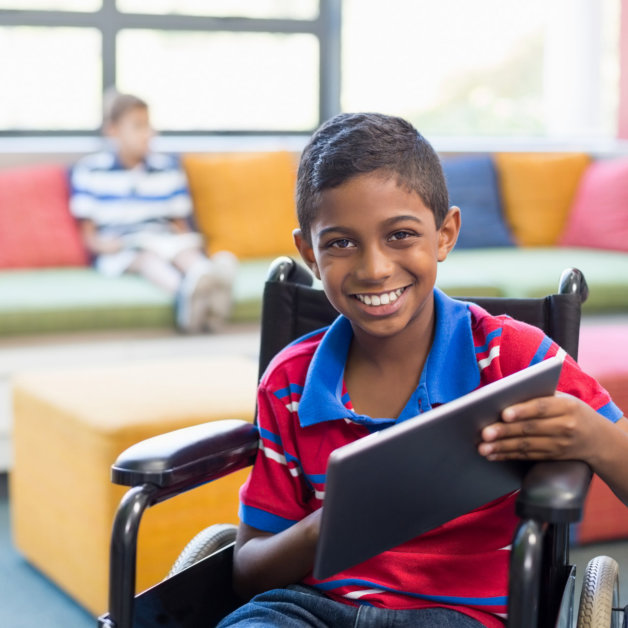Portrait of disabled schoolboy on wheelchair using digital tablet in library at school